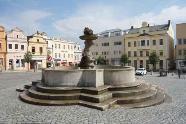 Co by to bylo za náměstí, kdyby tu nebyla kašna. Tahle se nazývá Koudelova kašna, protože ji podle pověsti nechal postavit pekař Koudela. Kašnu zdobí socha Tritóna, který nad hlavou nese kruhovou nádrž s delfínem.