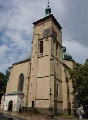 V rohu náměstí lze projít k raně gotickému kostelu Nanebevzetí Panny Marie. Na první pohled zaujmou nárožní hodiny, které z jedné strany mají 24hodinový ciferník a z druhé 12hodinový.