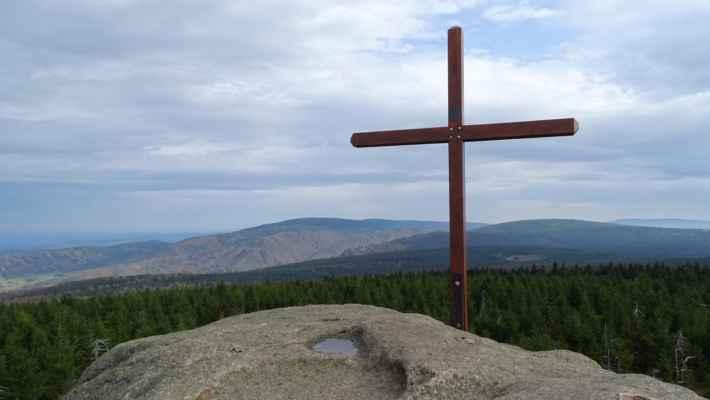 Kříž na Holubníku se Smrkem na pozadí vlevo. Pod ním vpravo je Paličník a ještě blíže Frýdlantské cimbuří, vedle něho Polední kameny a z druhé strany kříže je Smědavská hora