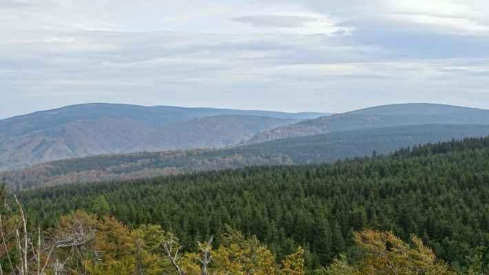 Vzadu se vlevo od Smrku táhne Velký Jizerský hřeben do polské části k nejvyšší hoře Jizerek Vysoké Kopě. Pod Smrkem je Tišina, uprostřed je pod horizontem Paličník, blíže Frýdlantské cimbuří a vpravo výše Polední kameny, a za nimi vpravo Smědavská hora